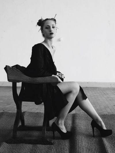 Portrait Of Sensuous Woman Wearing Dress While Sitting On Chair Against Wall