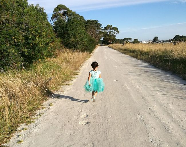 Full Length Child Childhood One Person Sunlight Tree One Girl Only Rear View Nature Children Only People Outdoors Playing Day Real People Little Princess Cute Little Girl Blue Child At Play In Mid Air  Country Road Countryside Glamour Country Girl