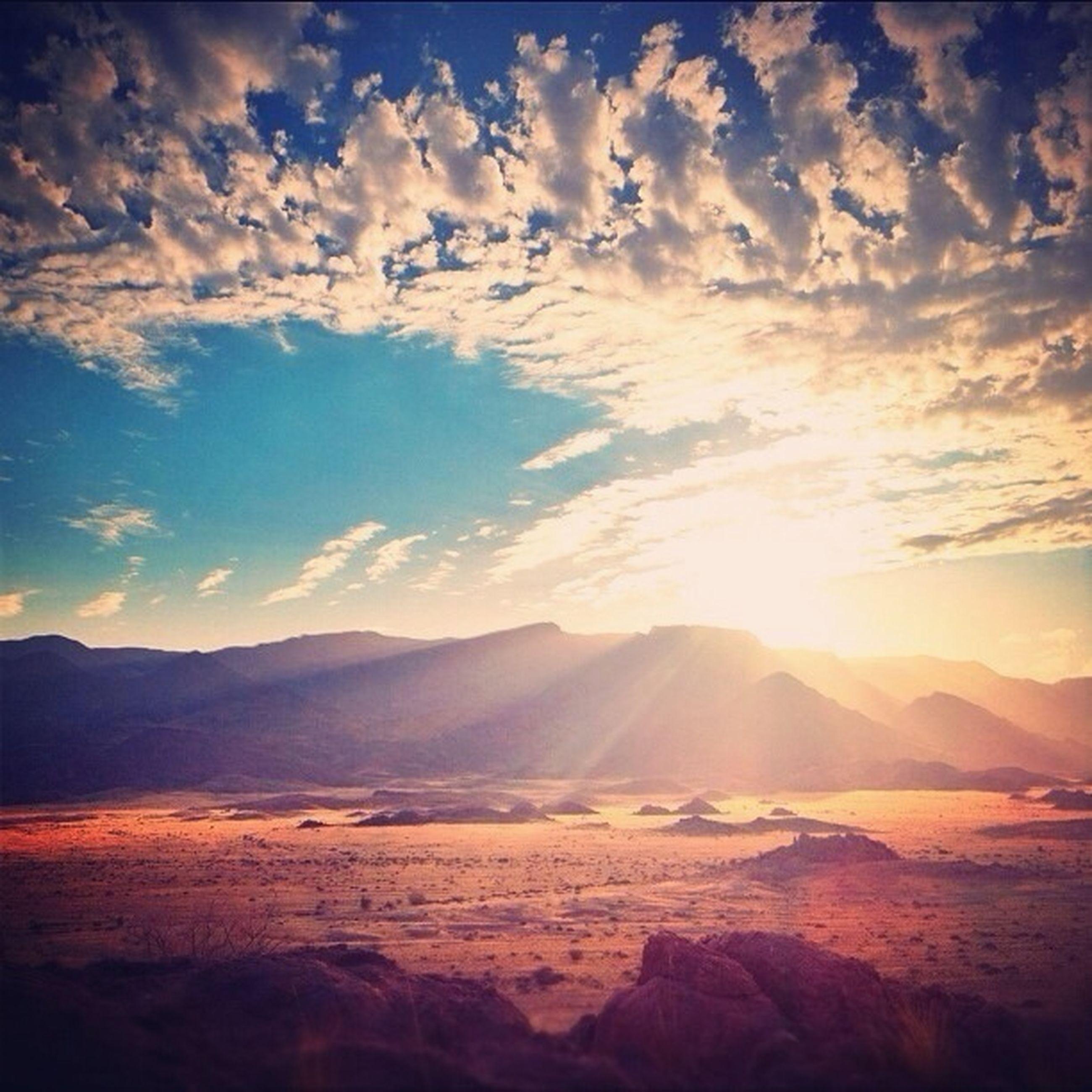 tranquil scene, mountain, scenics, tranquility, sky, landscape, beauty in nature, mountain range, cloud - sky, nature, sunset, sun, sunlight, cloud, non-urban scene, sunbeam, idyllic, remote, physical geography, horizon over land