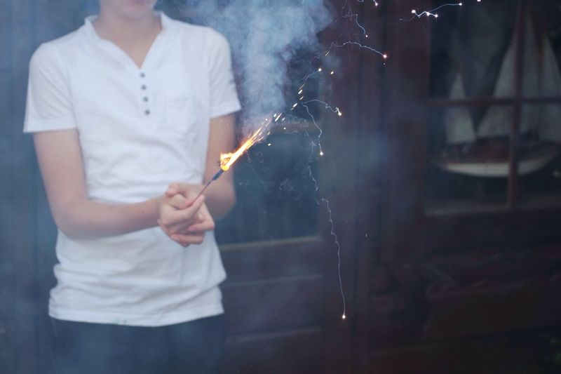 Midsection of boy holding burning sparkler amidst smoke