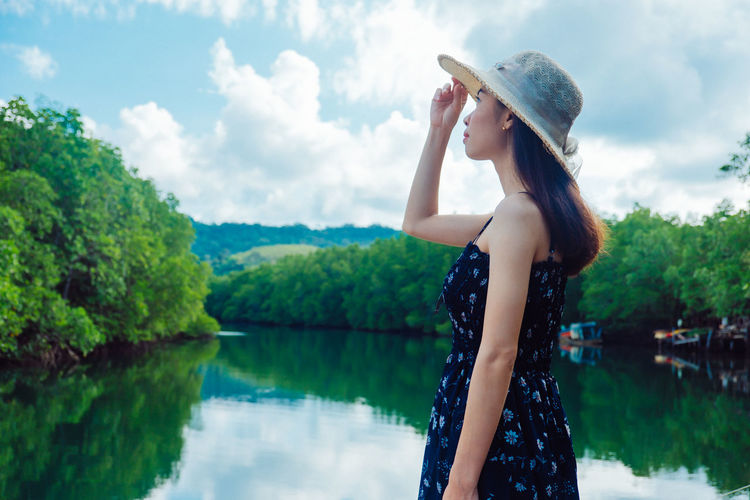 Woman wearing hat looking up while standing at shore