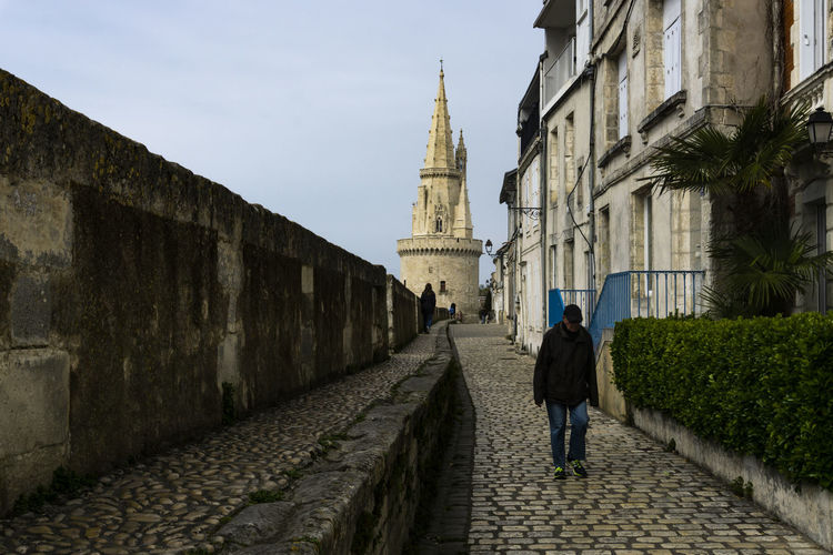 strolling in La Rochelle Architecture Building Exterior Built Structure Direction Real People Rear View The Way Forward Building Full Length One Person Lifestyles Walking Footpath Sky Day Wall Men Outdoors La Rochelle, France Bretagne Travel EyeEm Gallery Diminishing Perspective Streetphotography Cobblestone Cobblestone Streets Exceptional Photographs Strolling The Street Photographer - 2019 EyeEm Awards