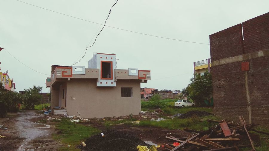 Houses by buildings against sky in city