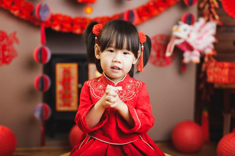 Portrait of cute girl holding red umbrella