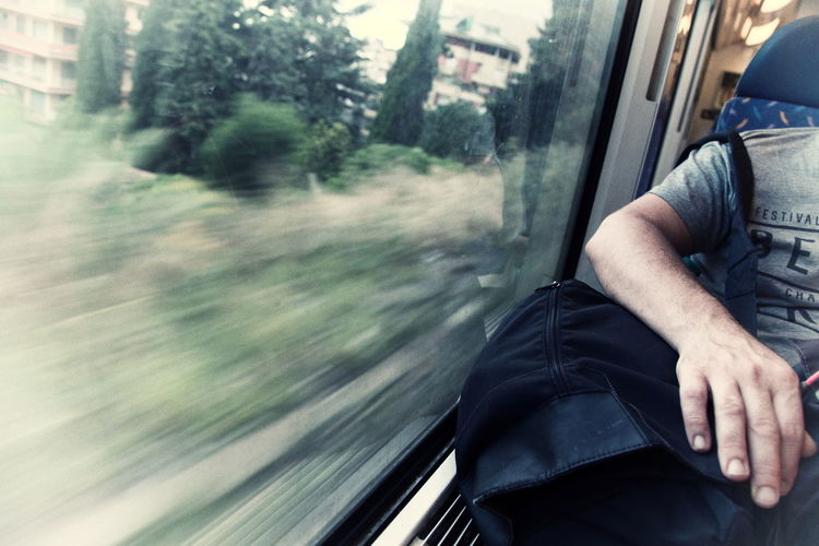 Cropped image of man sitting with luggage by window in train