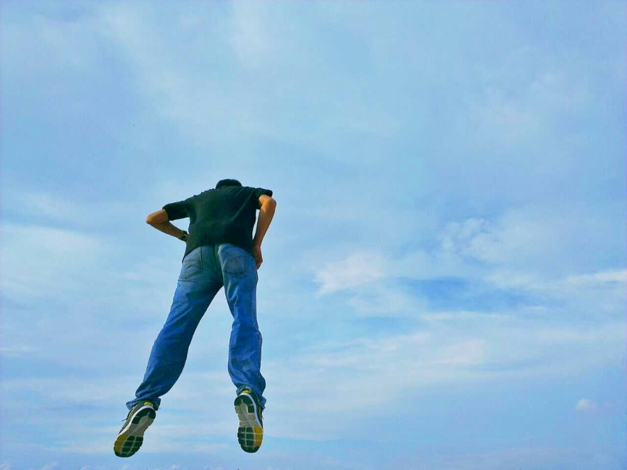 Low angle view of man floating in sky