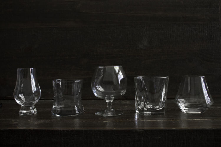 Collection of elegant drink glasses isolated on a dark background. Table Glass Transparent Glass - Material Empty Drinking Glass Still Life Food And Drink Crystal Glassware Whiskey Whisky Drink Bar Glassware Tableware Food Food And Drink Dark Old Vintage