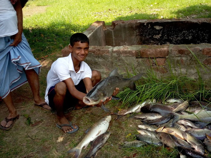 Smiling young man with fish in water