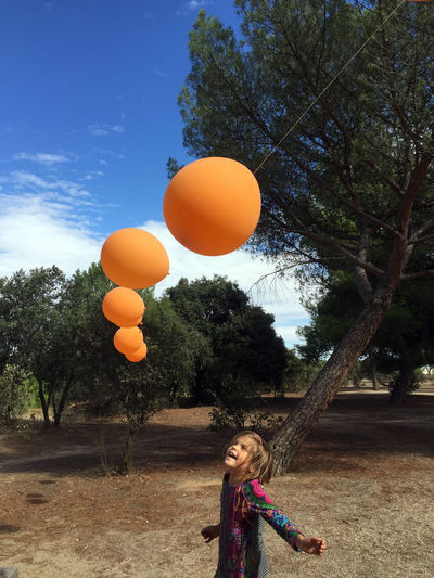 Girl happy with ballons Plant Balloon Childhood Orange Color Real People Leisure Activity Lifestyles Happiness Smiling Hair Innocence Portrait Girls Party Outdoors Child Day One Person Tree Playing Moments Of Happiness