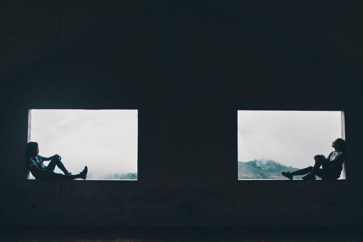 Side view of friends sitting window