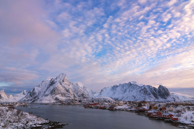 Scenic view of sea by snowcapped mountains against sky during sunset norway