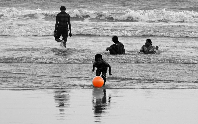 Child's Play on Beach Balance Beach Beach Photography Enjoyment Full Length Fun Horizon Over Water Leisure Activity Lifestyles Men Outdoors Real People Rear View Recreational Pursuit Sea Standing Vacations Water Wave Weekend Activities
