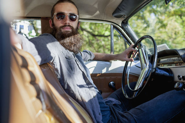 Looking across the front seat of bearded man in a vintage car
