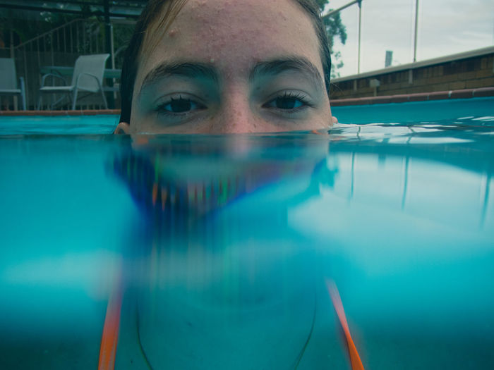 Close-up portrait of girl swimming in pool