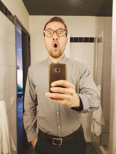 Portrait of man using mobile phone in bathroom