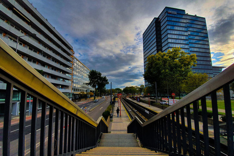 Footbridge amidst buildings in city against sky