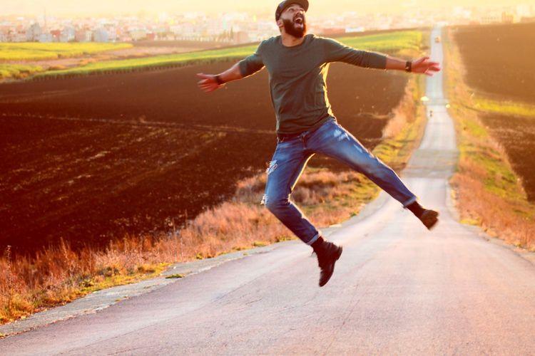 Full length of man jumping on road