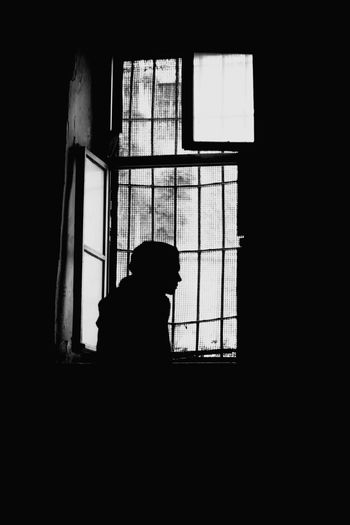 Silhouette man looking through window