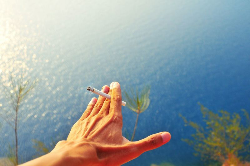 Cropped Hand Of Man Holding Cigarette Over Sea