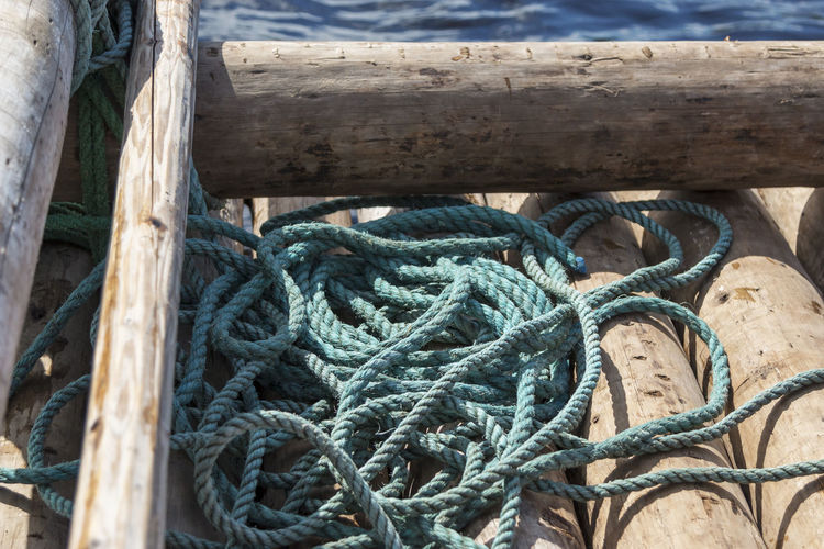 Close-up of rope on a raft Rope Nautical Vessel Raft Rafting Tied Knot Wood - Material Outdoors Close-up No People Backgrounds Twisted Strength Day Tied Up Connection Water Textured  High Angle View Pattern Nature Transportation Tangled Wooden Post River Klarälven