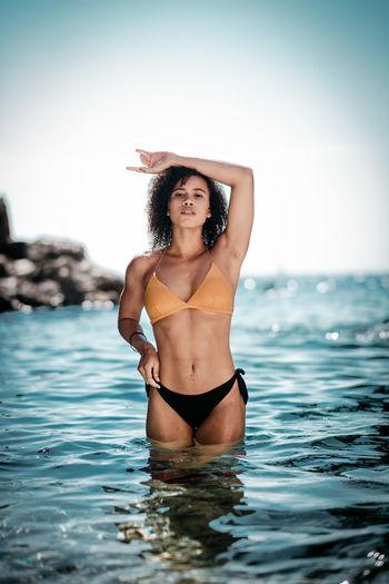 Portrait of sensuous young woman wearing bikini in sea