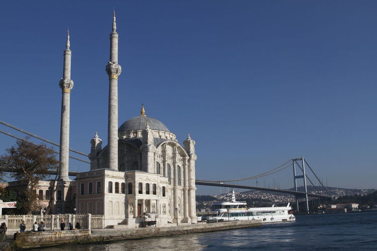 Ortakoy mosque by bosphorus bridge over strait against clear blue sky