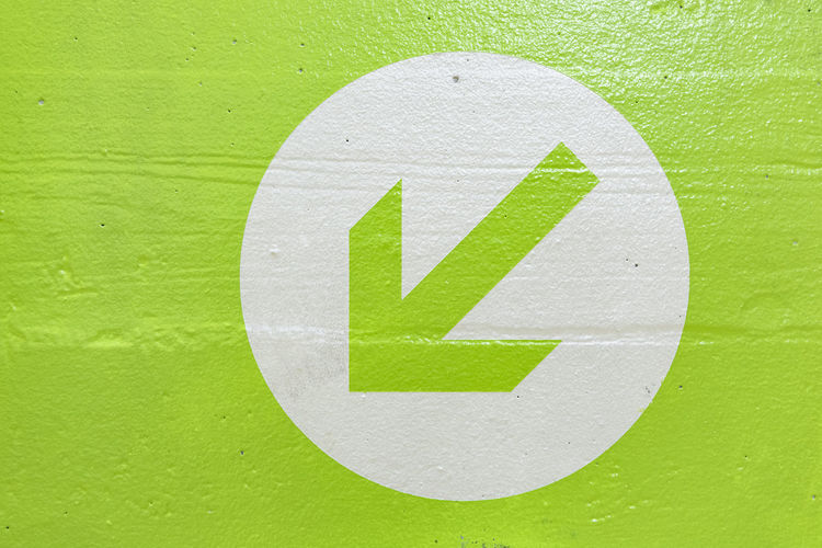 Close-up of arrow sign on green wall