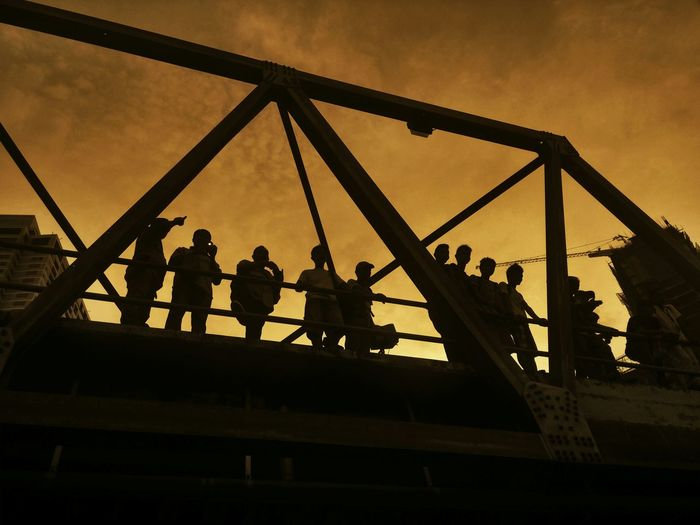 Low angle view of silhouette men on bridge against sky