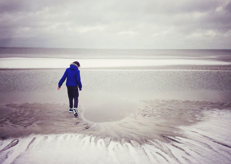 Rear view of girl walking at beach against cloudy sky during winter
