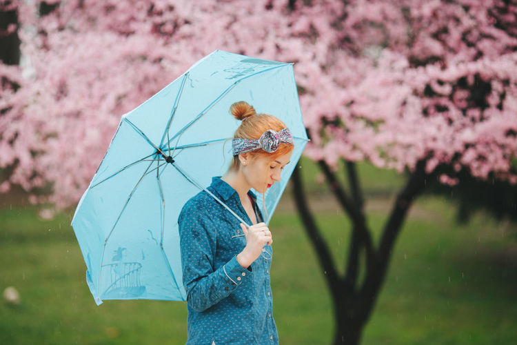 Midsection of woman with pink umbrella standing in rain