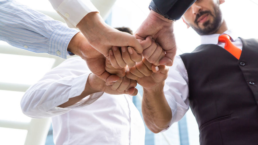 Close-up of colleagues fist bumping at outdoors