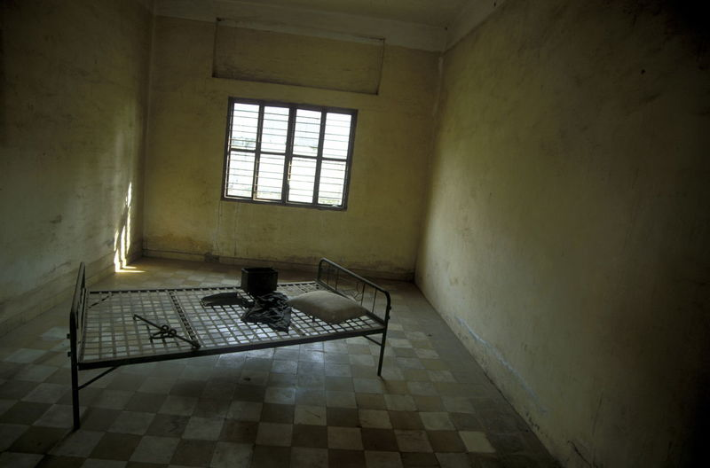 Bed On Checked Patterned Floor At Prison Cell