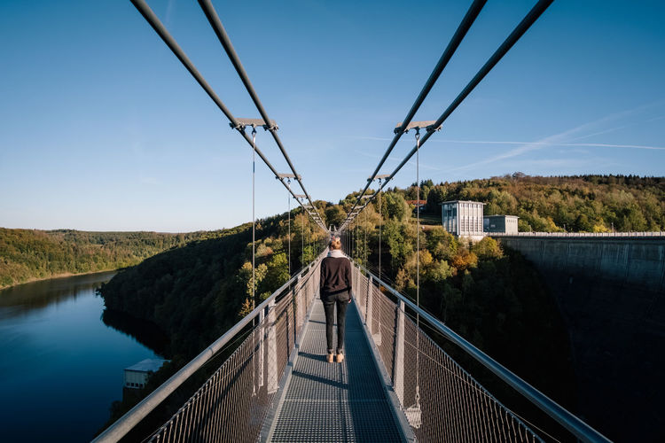 Rear view of woman on footbridge against sky