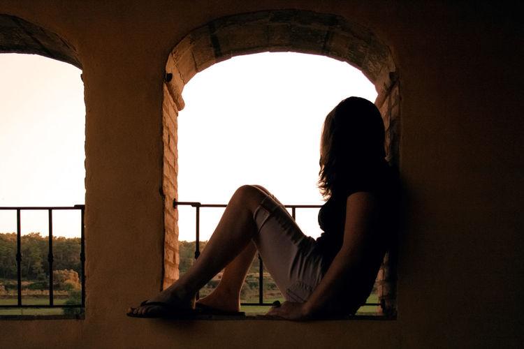 Woman Sitting Under Arch