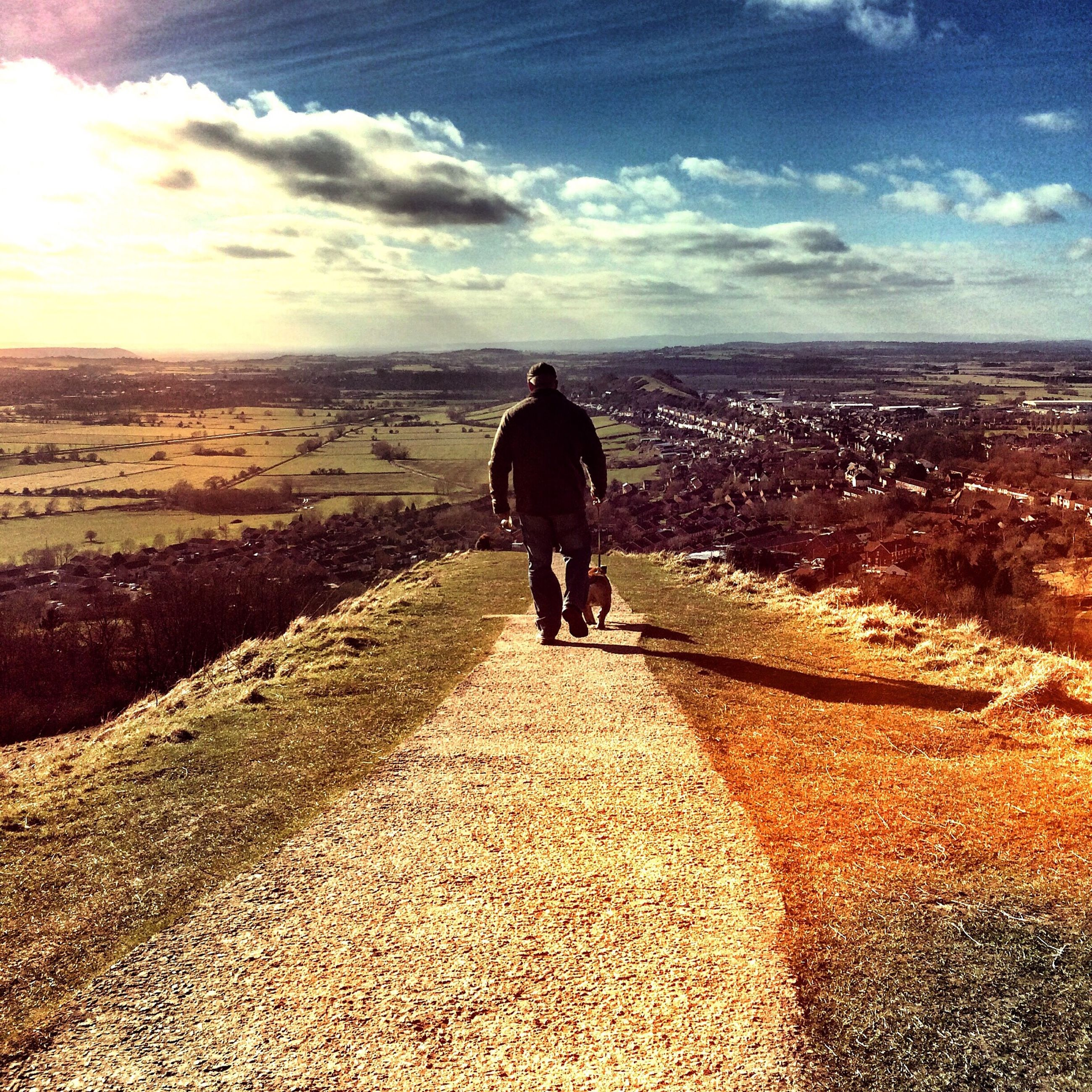 sky, rear view, full length, walking, lifestyles, the way forward, cloud - sky, leisure activity, men, person, standing, cloud, casual clothing, sunlight, road, outdoors, landscape, day