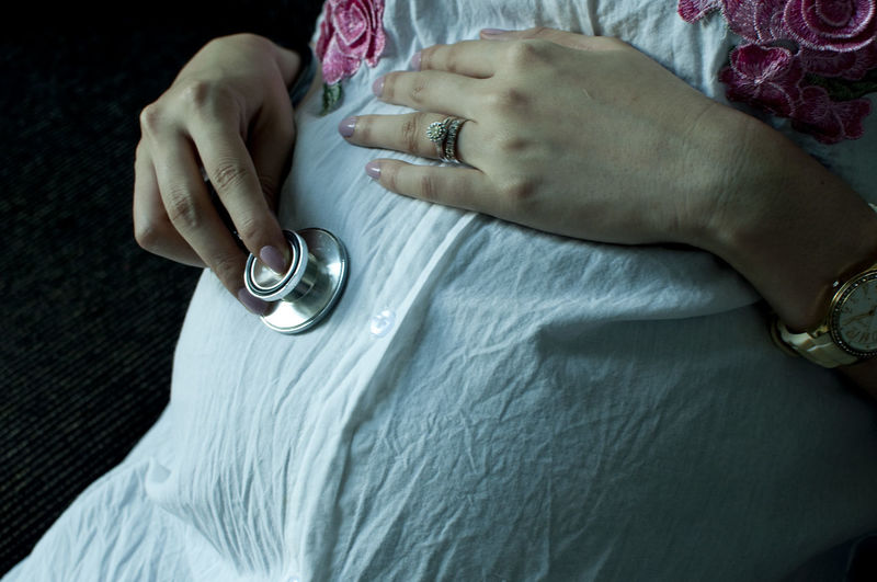 Midsection Of Pregnant Woman Holding Stethoscope