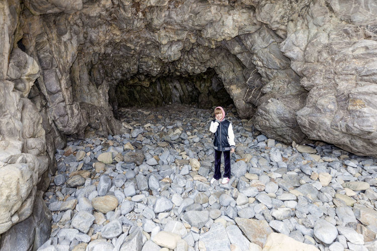 Portrait of smiling teenage girl standing against cave