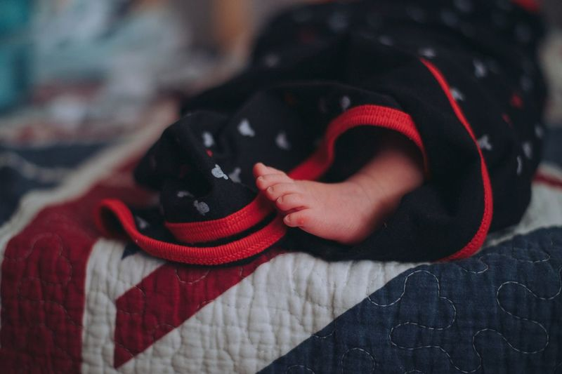 Close-up of baby girl on bed