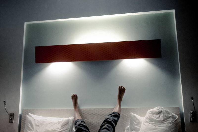 Low section of woman relaxing on bed against wall