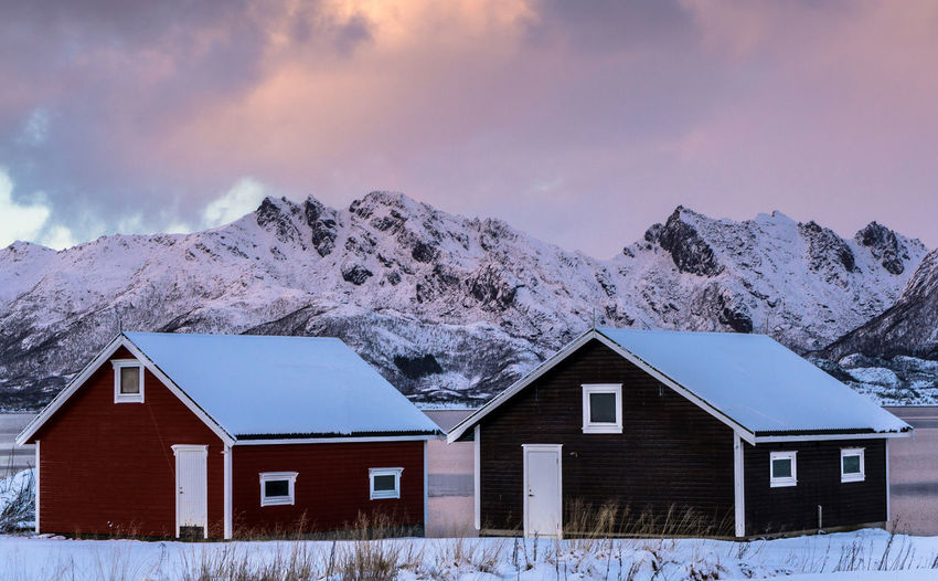 Houses against snowcapped mountains during sunset