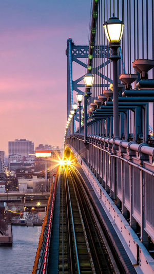 Illuminated Train On Track By Bridge Over River In City During Sunset