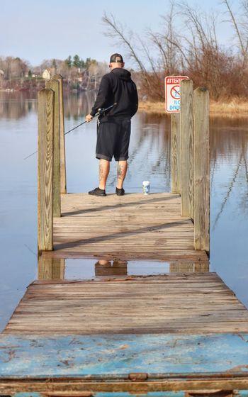 Full length of man standing on wooden post against sky