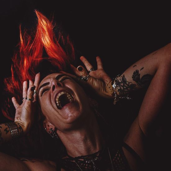 View of woman shouting against black background