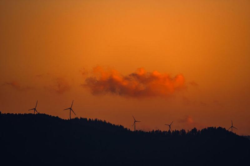 Silhouette of wind turbines on field against orange sky