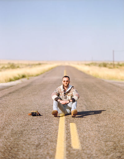 Portrait of man sitting on road against sky