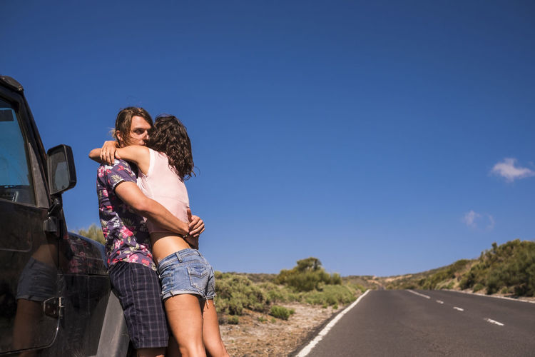 Young couple embracing on road against sky during sunny day