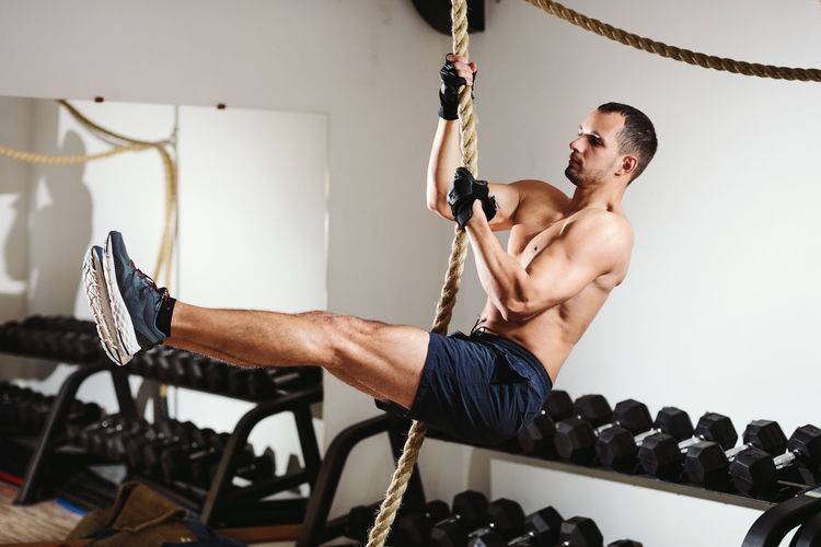 Side View Of Shirtless Male Athlete Training In Gym