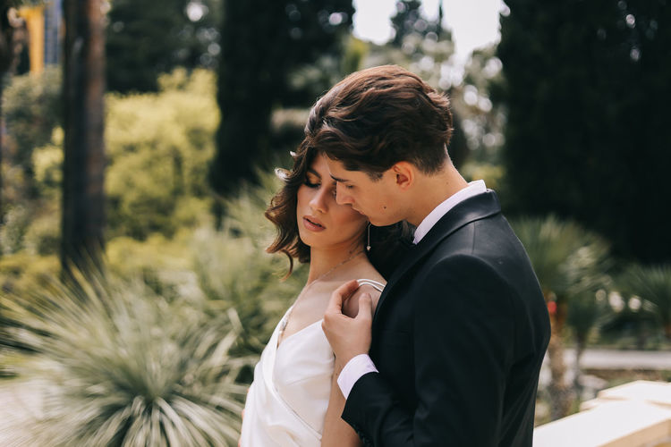 A beautiful couple in love, bride and groom in wedding clothes, walk and pose in the park in nature