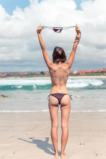 Rear view of seductive woman standing at beach against sky