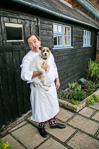 Full length portrait of man with dog standing outdoors